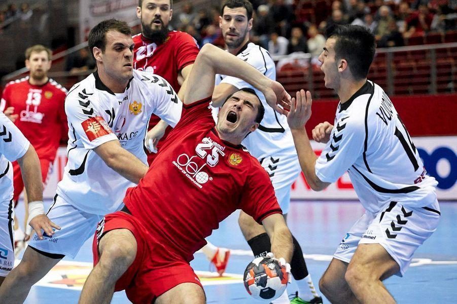Sergey Shelmenkon (Russie) à la lutte avec Milos Vujovic ( Montenegro) lors du championnat d'Europe de handball messieurs, en Pologne.
