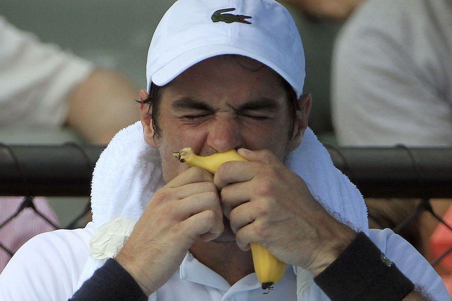 Le Français Jeremy Chardy tente de manger une banane lors d'une pause alors qu'il affronte Ernests Gulbis à l'Open d'Australie.