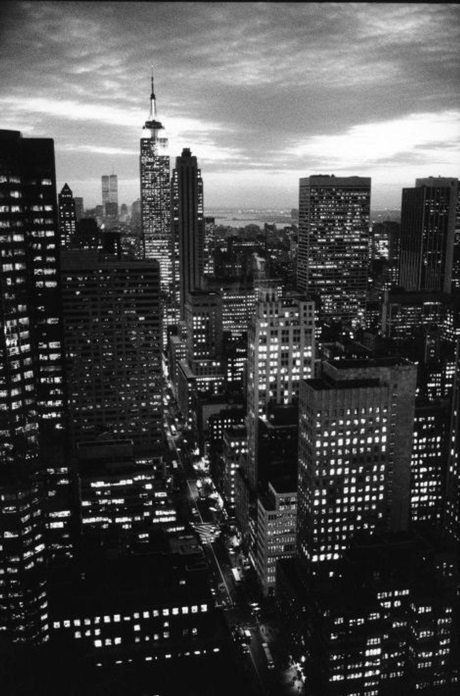 """Un champ de colonnes géantes de béton gris, de verre et de brique rouge, que dominent alors l'Empire State Building et les tours jumelles du World Trade Center. C'est la ville qui touche le ciel, et qu'on découvre la tête vers les étoiles... Celle qui faisait crier """"America !"""" aux immigrants européens qui rêvaient de liberté. New York, la cité verticale à l'énergie sans pareille, où se mêlent les cultures du monde et les envies d'impossible. Pour célébrer la 1000e photo exposée dans la grande galerie de Paris Match, la rédaction vous propose six clichés intemporels."""
