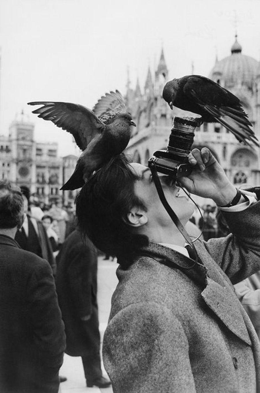 """Alain delon joue les touristes sur la place Saint-Marc alors qu'il se trouve à Venise pour les essais du film """"Marco Polo"""" de Christian-Jaque, le 1..."""