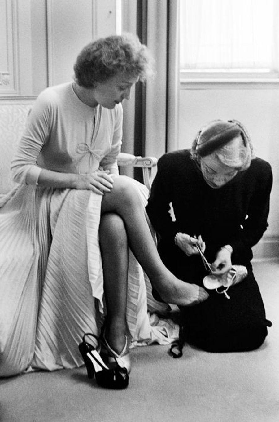 New York, 29 juillet 1952, Edith Piaf épouse Jacques Pills. Son témoin, Marlène Dietrich, agenouillée à ses pieds, perce de nouveaux trous dans...