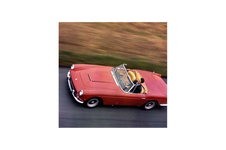 Photo prise à l'occasion du Salon de l'auto 1962, Jean-Paul Belmondo au volant de sa Ferrari 250 GT, roulant à 200 km/h.