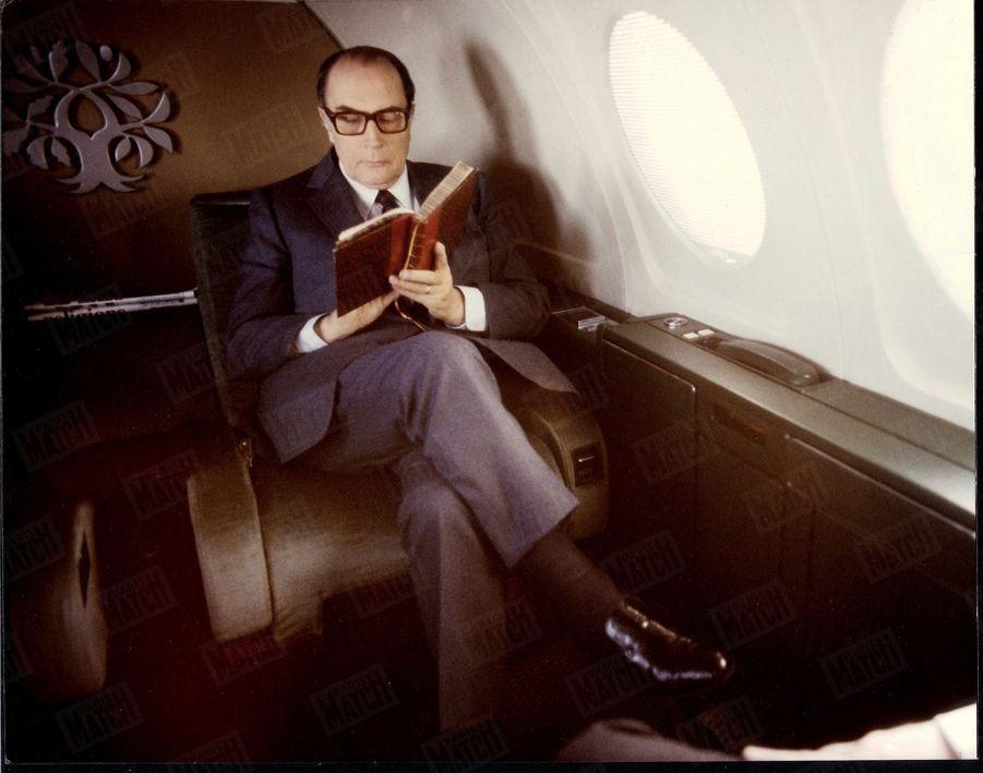 """François Mitterrand lisant un livre à bord de son avion Mystère 50 baptisé """"Rambouillet"""" revenant de Toulouse où il a célébré le lancement officiel de l'Airbus 320. On voit au-dessus de sa tête son emblême : des branches de chêne (la robustesse) et d'olivier (la paix) sur un tronc commun, le 13 mars 1984."""
