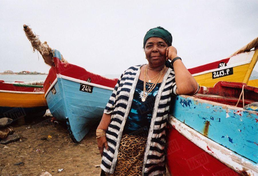 La chanteuse Cesaria Evora accoudée à un bateau de pêche sur une plage de l'île de Sao Vicente au Cap-Vert, en août 2003.