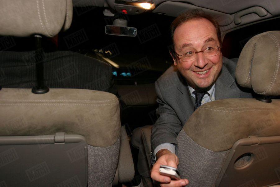 François Hollande souriant après avoir remporté le référendum interne du Parti socialiste sur la Constitution européenne, dans une voiture entre Tulle et Paris, en décembre 2004.
