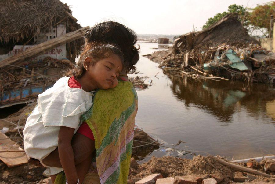 Une femme portant dans ses bras sa fillette endormie, devant les maisons détruites du village de pêcheurs de Nagapattinam, après le tsunami géant qui a déferlé sur les côtes de l'Asie du Sud-Est et de l'Afrique faisant quelque 230 000 morts, le 26 décembre 2004.