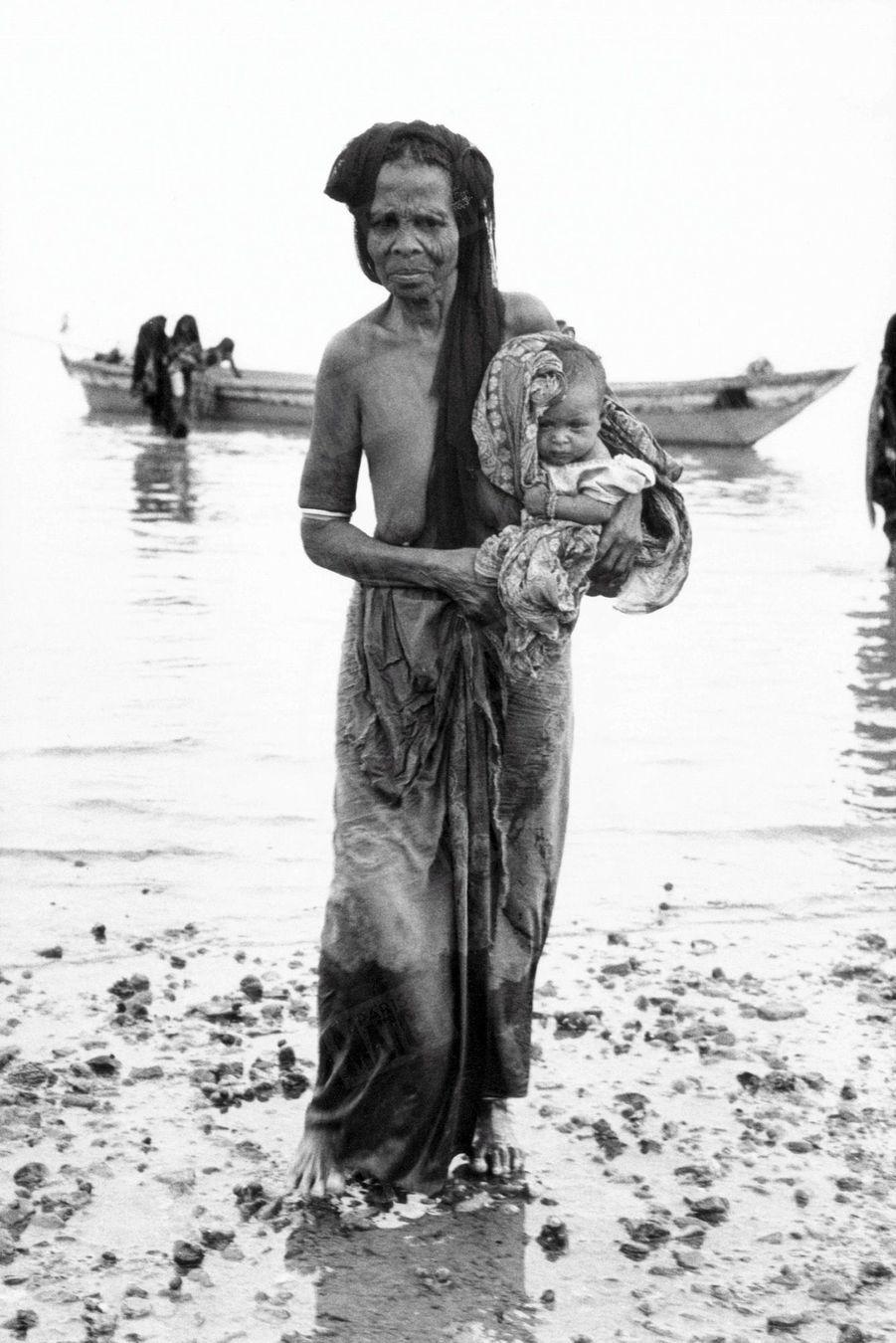 Une réfugiée érythréenne avec un enfant dans les bras aborde les côtes du Yémen, fuyant les combats qui opposent son peuple à l'Ethiopie, en 1977.