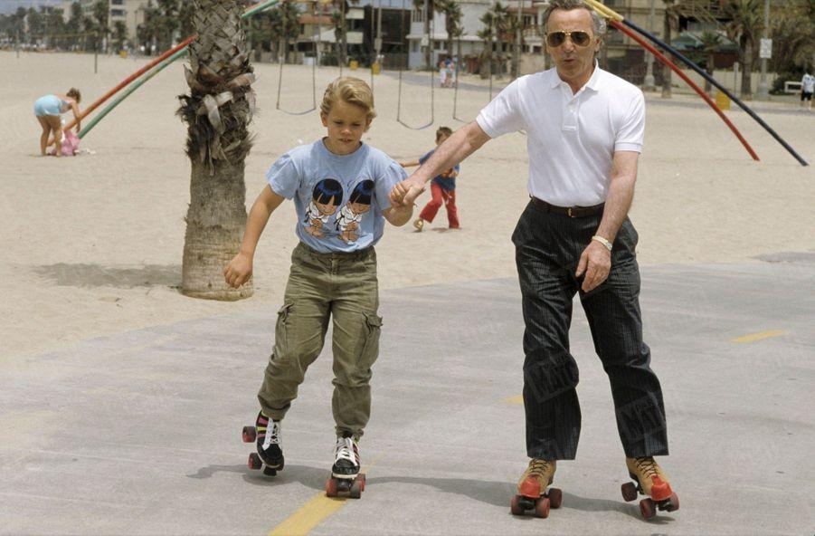 Charles Aznavour faisant du patin à roulettes en compagnie de son fils Nicolas, 11 ans, sur la promenade de Santa Monica, en Californie, le 7 juillet 1987.