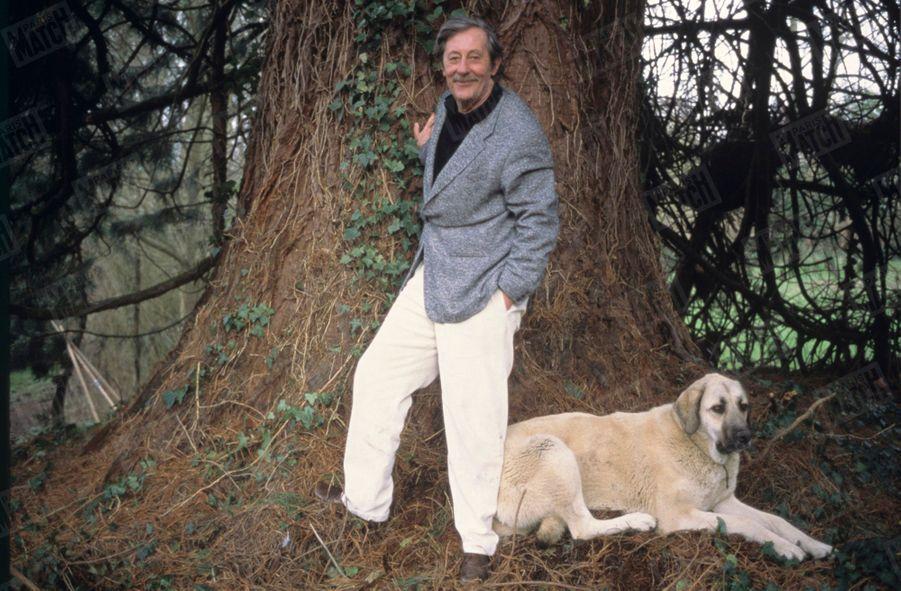 Jean Rochefort, accompagné de son chien Yol, un berger d'Anatolie, pose au pied d'un arbre centenaire dans le jardin de sa maison près de Paris, en février 1995.