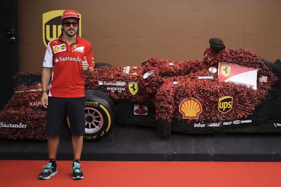 Le pilote Fernando Alonso pose devant une réplique en plante de sa voiture Ferrari, en marge du Grand Prix de Singapour.