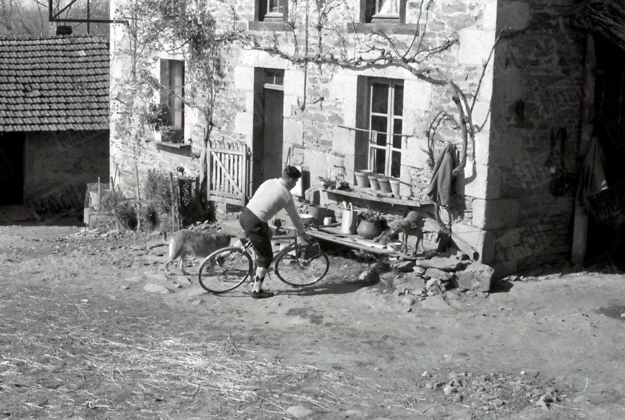 Raymond Poulidor sur son vélo chez lui dans la ferme de Saint-Léonard-de-Noblat, dans le Limousin, en mars 1961.