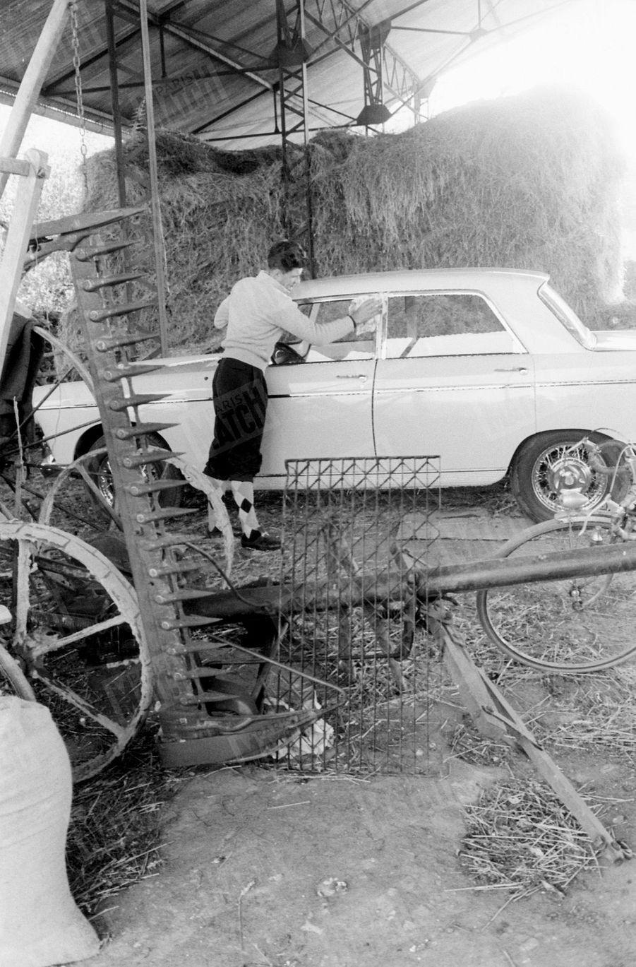 Raymond Poulidor entretient sa voiture Peugeot 404, dans la grange de la ferme de ses parents à Saint-Léonard-de-Noblat, dans le Limousin, en mars 1961
