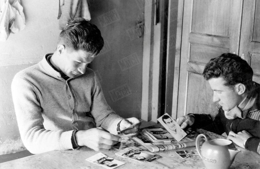 Raymond Poulidor et son frère passent en revue les photos de presse du champion en devenir, en mars 1961.