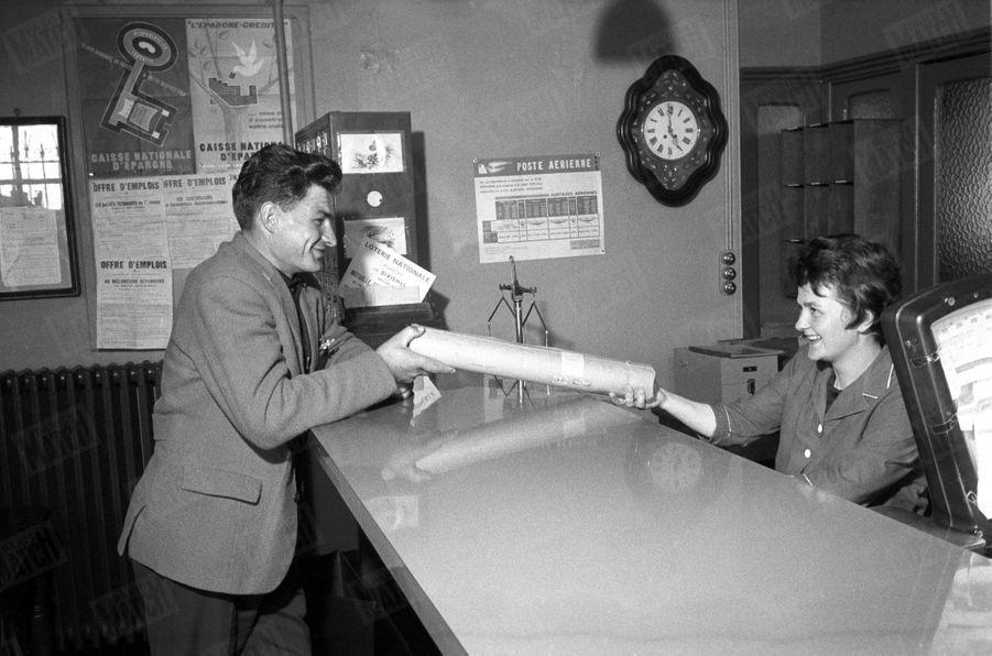Raymond Poulidor et son épouse Gisèle, dans le bureau de poste où elle est employée à Saint-Léonard-de-Noblat, dans le Limousin, en mars 1961.