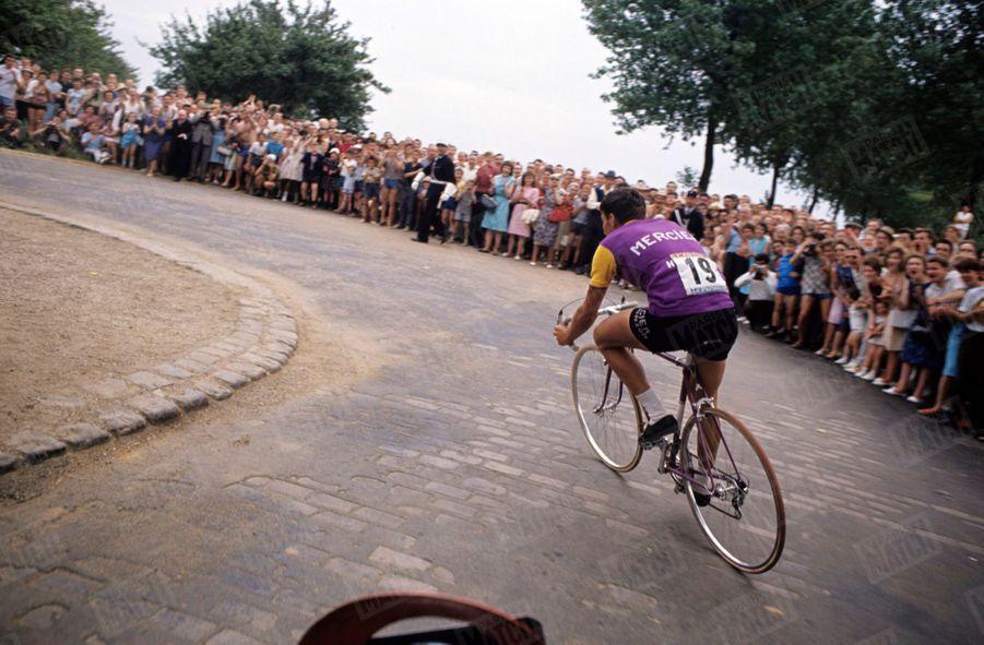 """« Pendant les 27,500 km de la course contre la montre entre Versailles et le Parc des Princes, les 600 000 spectateurs acclament Poulidor comme le vainqueur. Ici, à mi-parcours, son « radar ». (Antonin Magne qui lui parle par coups de klaxon) dit à Poulidor qu'Anquetil perd du terrain. La foule hurle : """"Vas-y, Raymond. Tu l'as"""" » - Paris Match n°798, 25 juillet 1964"""