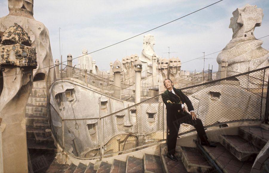 « Dali nous présente ici le Barcelone qui fascina son enfance, le Barcelone du « Modernisme », ce style qui au début du XX° siècle a été le pendant catalan et, ô combien plus riche, du « Modern' Style » de Paris. Ses maîtres : Luis Domenech y Montaner qui bâtit en 1908 le Palais de la musique catalane et surtout Antonio Gaudi, l'architecte de la Casa Mila (photo), paseo de Gracia et de la Sagrada Familia, le temple expiatoire de la Sainte Famille, la seule cathédrale vivante des temps modernes, malheureusement inachevée dont la façade flamboie dans la page suivante. Salvador Dali voit en Gaudi l'antidote au poison le plus funeste de notre siècle : Le Corbusier. Selon lui, l'architecture de demain ne sera ni clinique ni fonctionnelle à la façon du protestant Le Corbusier. Elle sera « molle et poilue » comme celle de Gaudi, catholique apostolique et romain.» - Paris Match n°1055, 26 juillet 1969