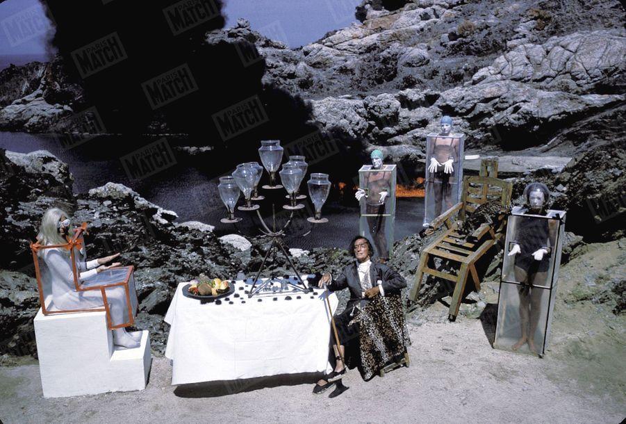« Pour recevoir la reine de l'Espace, Dali a mis un plastron de dentelles, mais conservé, aux pieds, ses espadrilles catalanes qui ne le quittent jamais. À droite, debout sur les rochers et dans l'eau : la garde royale amphibie des Vénusiens.» - Paris Match n°856, 4 septembre 1965