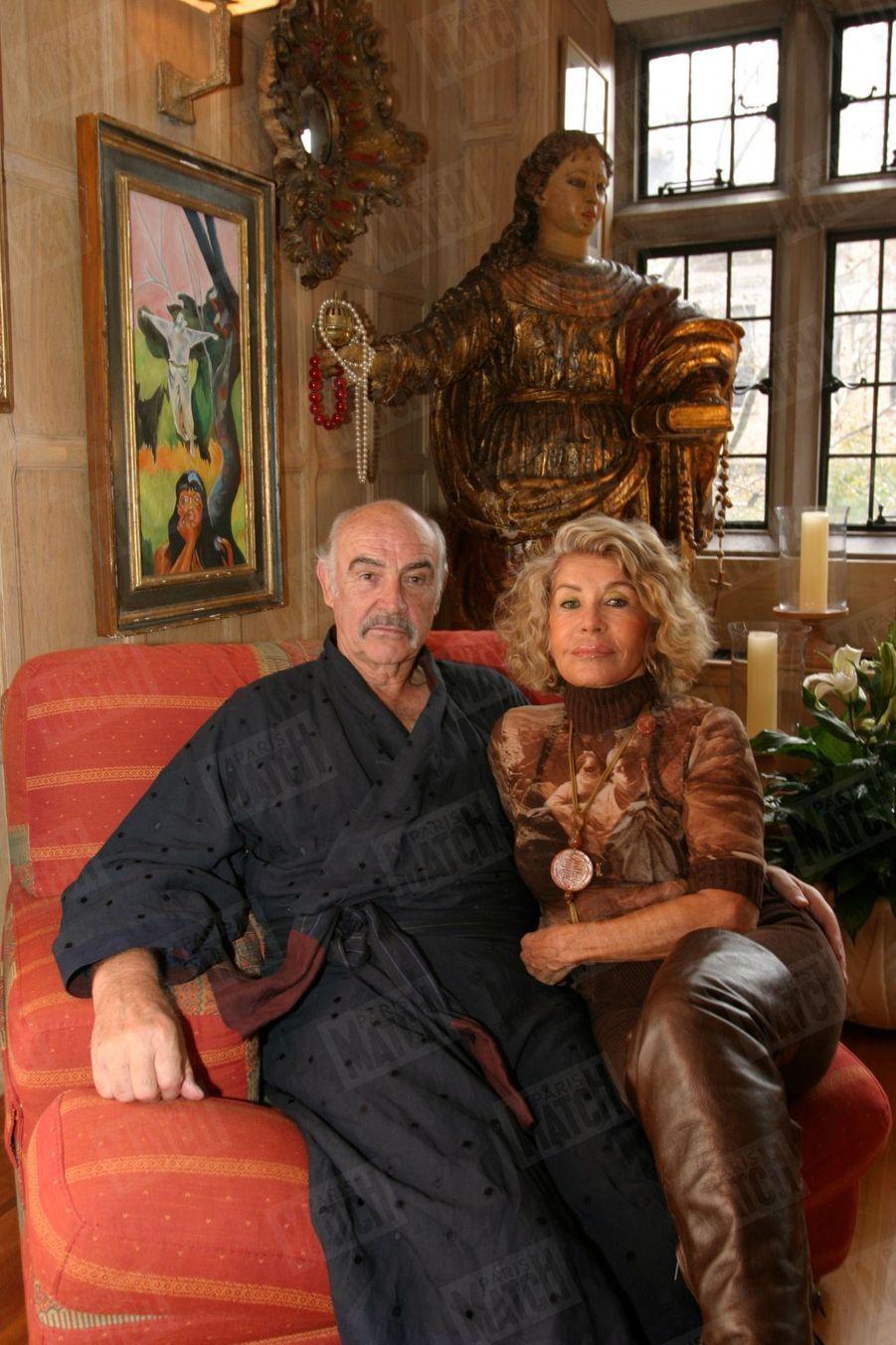 Sean Connery et son épouse Micheline dans le salon de leur appartement de Manhattan à New York en novembre 2004. Derrière eux, un tableau de Micheline et une statue du XVIIème siècle dont elle a restauré la tête.