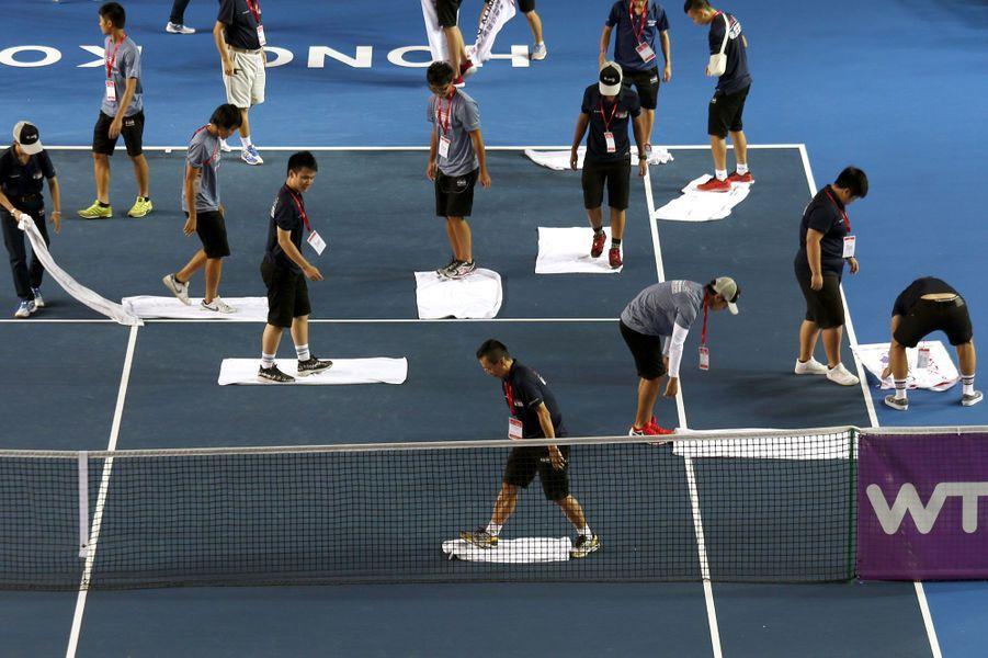 Lors du tournoi de tennis de Hong Kong, des assistants essuient comme ils peuvent le terrain après la pluie.