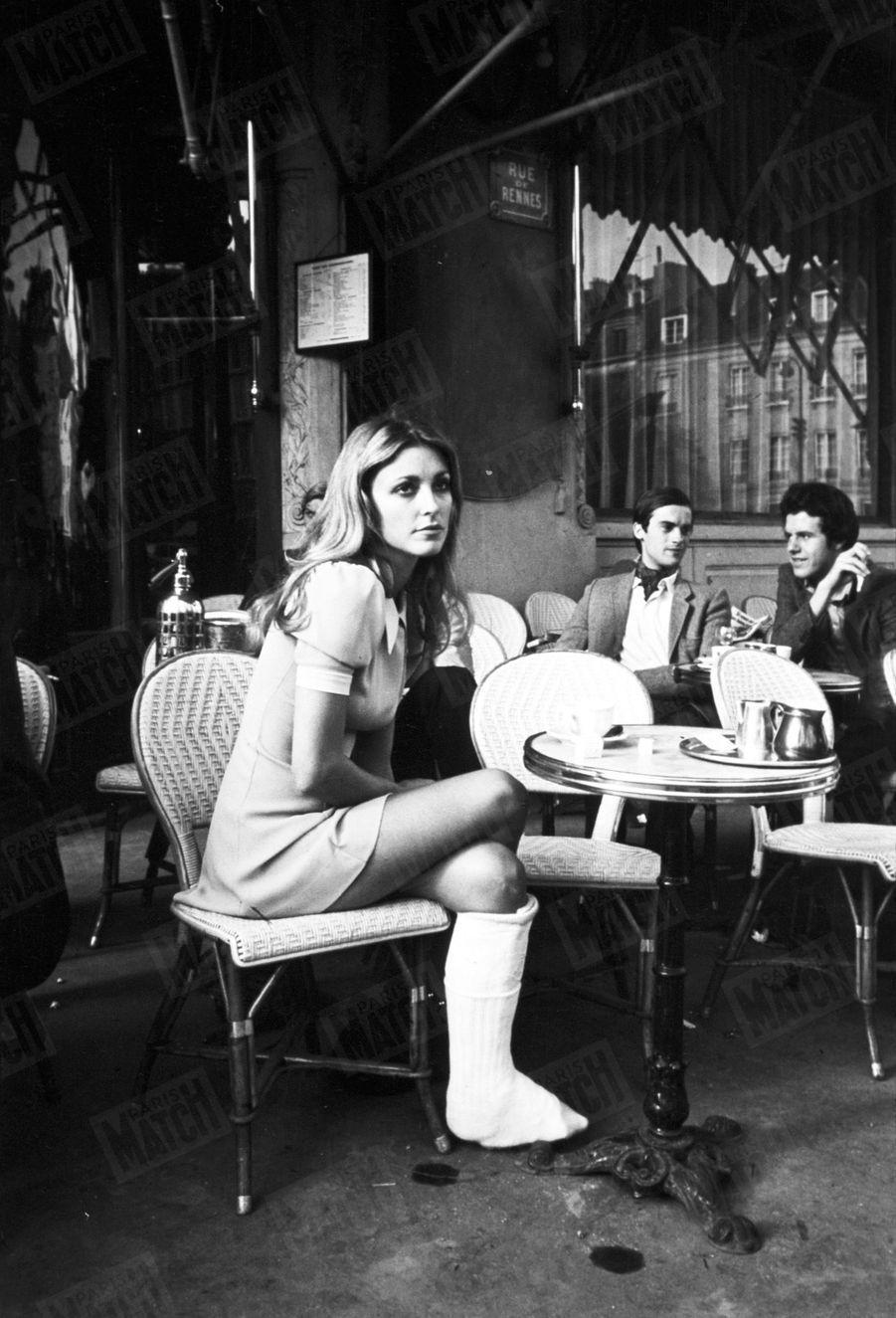 """Sharon Tate, lajambe plâtrée après une chute dans l'escalier de son hôtel, en terrasse du café """"Les deux Magots"""" àSaint-Germain-des-Prés,à Paris,en octobre 1968."""