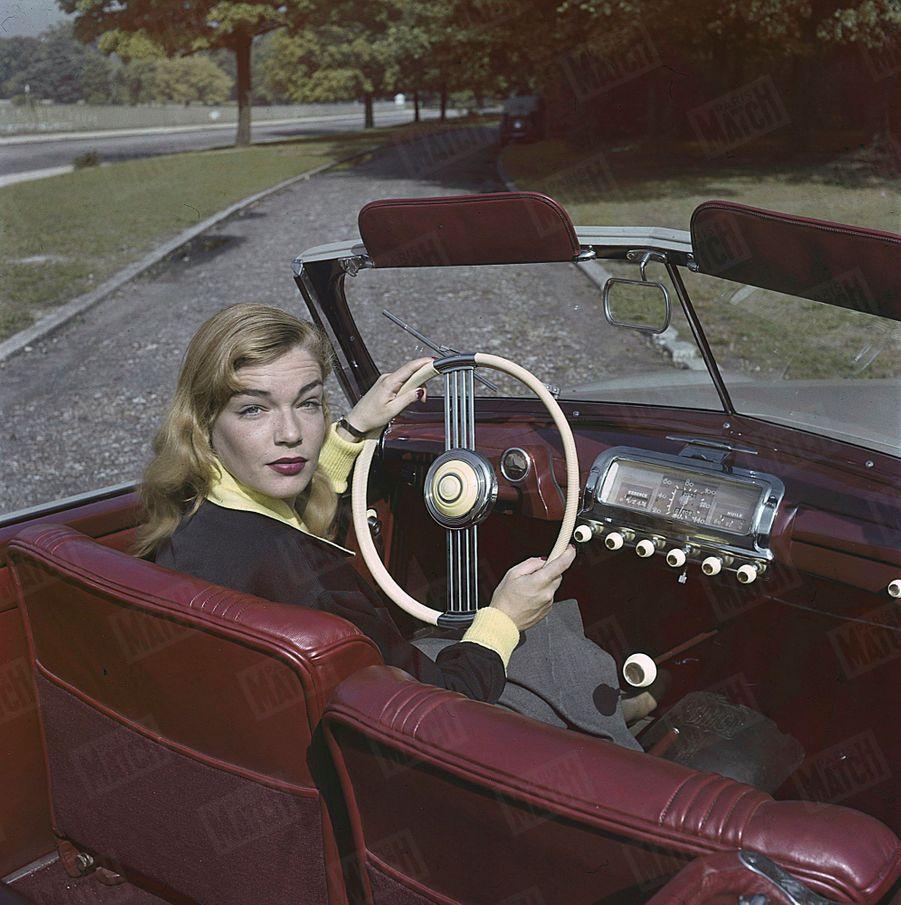 Simone Signoret pose à bord d'un cabriolet Simca Sport. (Photo non datée, années 1950)