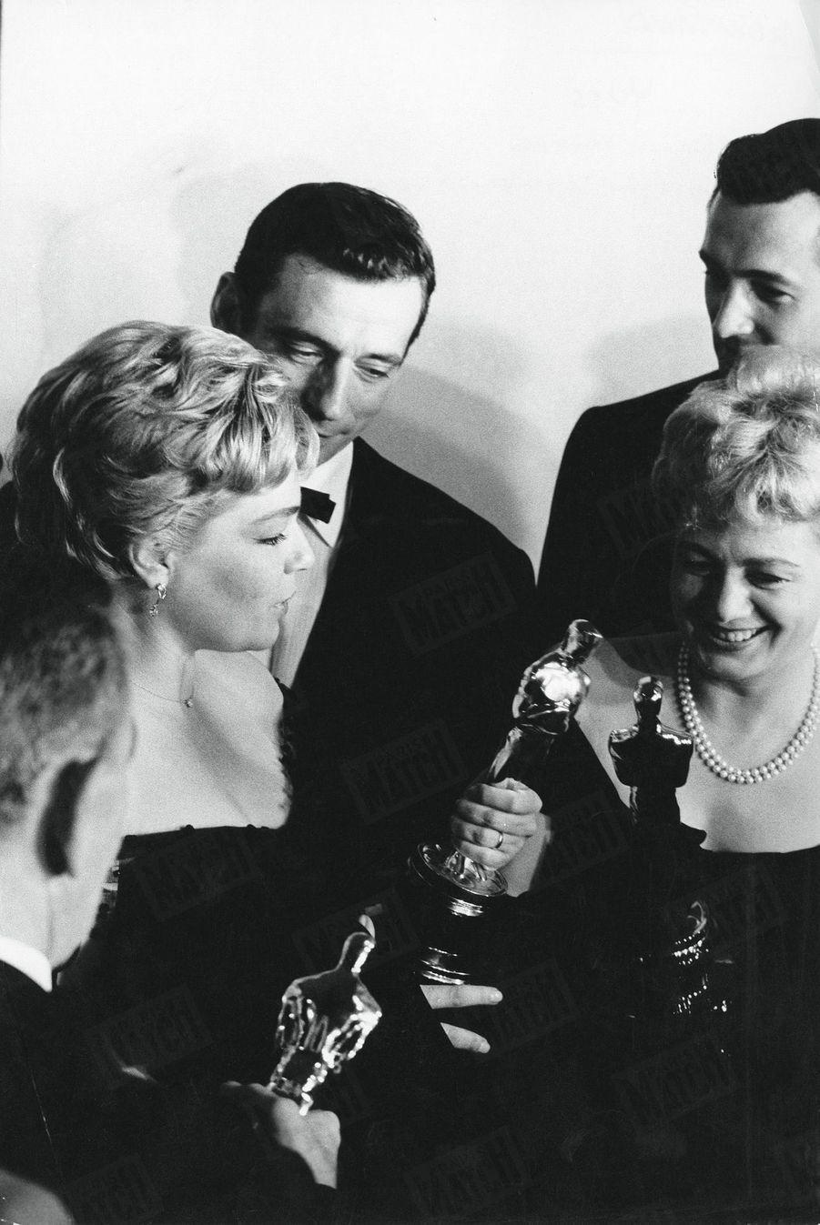 """Simone Signoret, oscar de la meilleure actrice pour le film """"Les chemins de la ville haute"""", entourée d'Yves Montand, Shelley Winters et Rock Hudson, à la cérémonie des Oscars à Hollywood, en avril 1960."""
