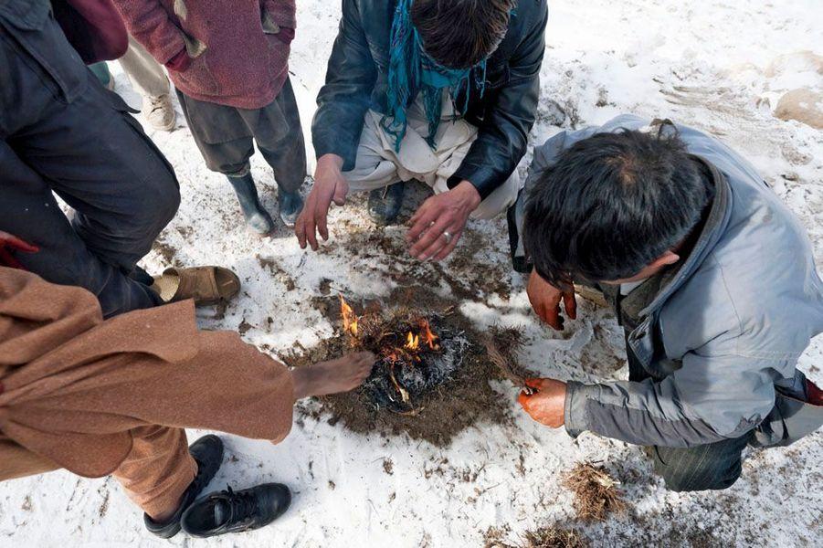 Un petit feu pour se réchauffer les pieds, mal protégés, et les mains, dépourvues de gants.