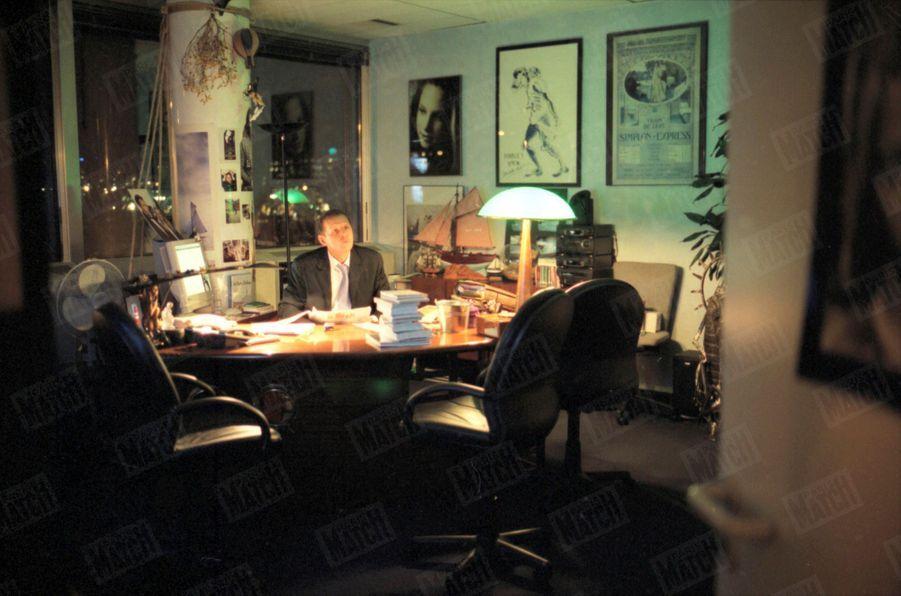 Patrick Poivre d'Arvor, dans son bureau de TF1, en décembre 2002. Autour du présentateur, plusieurs photos de sa fille Solenn.