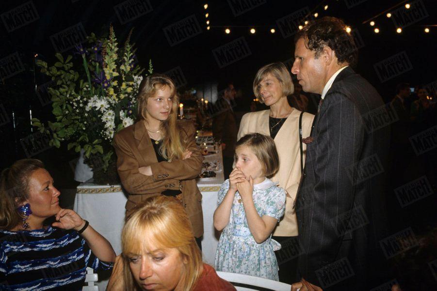 Patrick Poivre d'Arvor, entouré de son épouse Véronique et de ses filles Morgane, 9 ans, et Solenn, 15 ans, lors de la réception donnée pour ses dix ans de présentation du 20H, aux serres d'Auteuil en juillet 1990.
