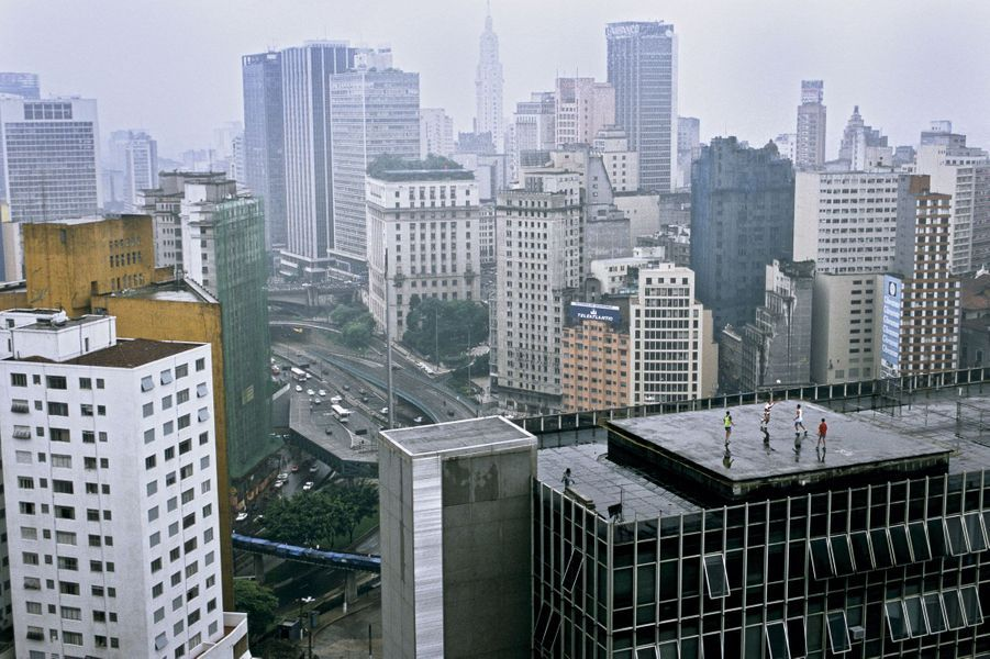 """Sao Paulo en 1997, en plein boom de l'immobilier. """"J'étais en train de photographier le panorama, célèbre pour ses gratte-ciels, raconte Christopher Pillitz. Et puis, à 200 mètres de moi, j'ai découvert ces jeunes jouant au foot sur le toit d'un immeuble de bureaux d'au moins trente étages. J'étais estomaqué. Il faut être très adroit pour faire ça sans perdre son ballon!"""""""