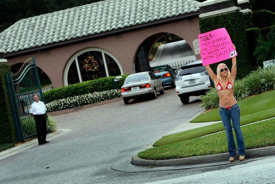 """Une """"supportrice"""" de Tiger Woods devant sa résidence de Floride, tenant une pancarte : """"Tiger, on m'a offert 500 000 $, mais je vais la fermer !"""""""