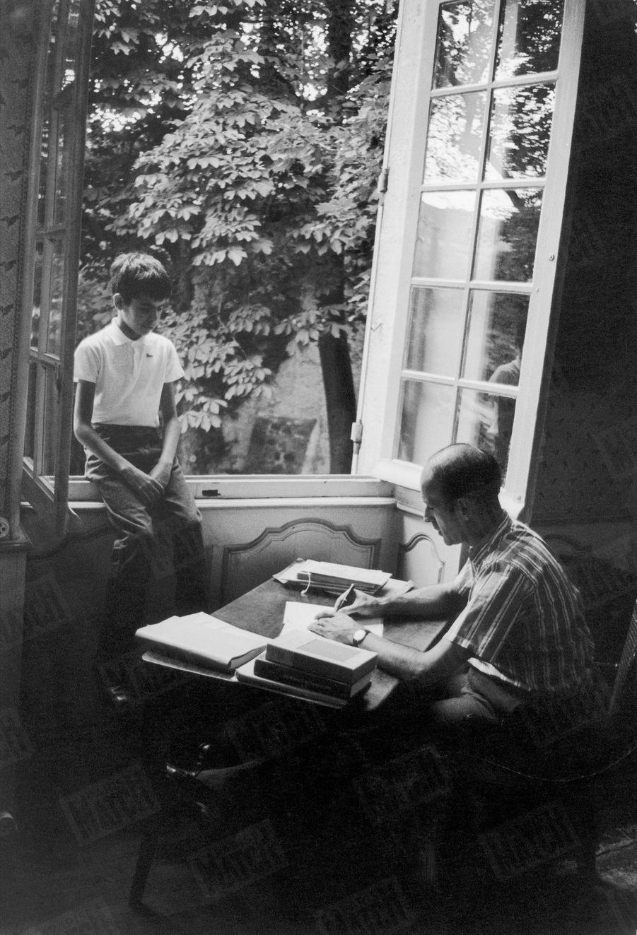 Valéry Giscard d'Estaing écrit à sa table de travail en présence de son fils Henri, 10 ans, dans la maison familiale du Puy-de-Dôme, en août 1967.