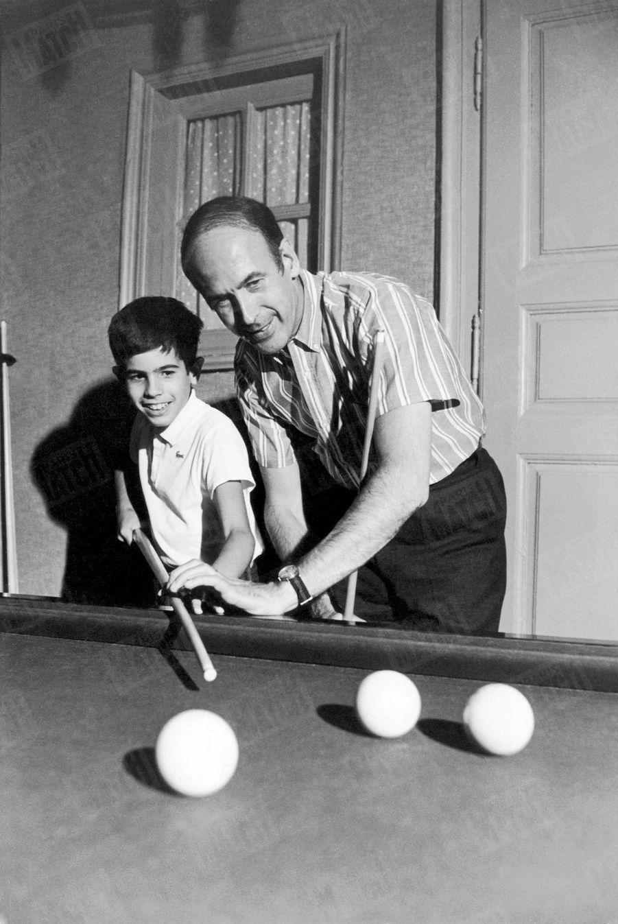 Valéry Giscard d'Estaing joue aux billard avec son fils Henri, 10 ans, dans la maison familiale de Chanonat, dans le Puy-de-Dôme, en août 1967.