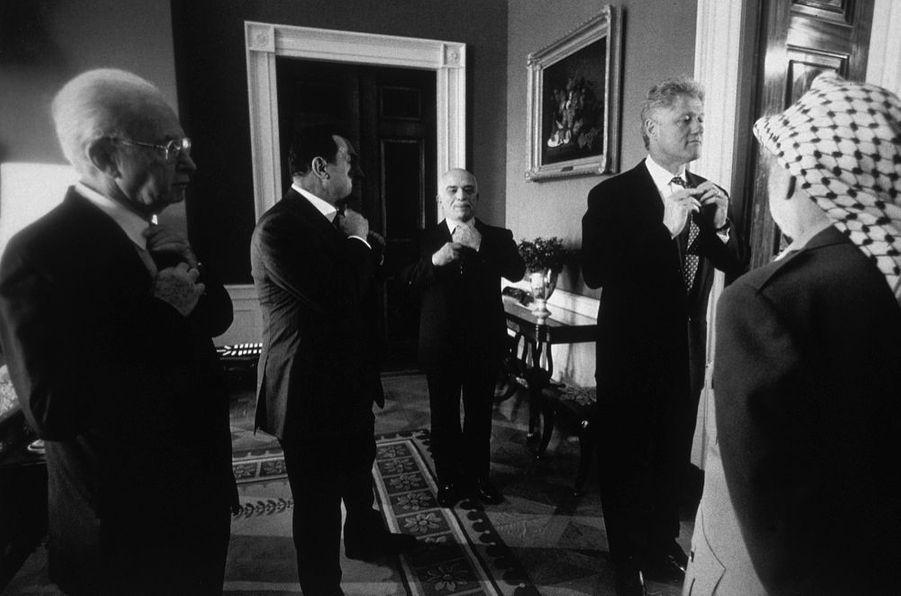 Les acteurs préparent leur entrée en scène. Ils viennent de discuter pendant des heures pour modifier quelques lignes dans un document de 400 pages. Le 27 septembre 1995, avant de ratifier les accords sur le désengagement militaire israélien dans les Territoires occupés, Yitzhak Rabin, Hosni Moubarak, Hussein de Jordanie, Bill Clinton et Yasser Arafat traversent l'antichambre vers le salon Est de la Maison Blanche. Un conseiller fait remarquer à Bill Clinton que sa cravate est de travers. Aussitôt, sous le regard du Palestinien, qui n'a pas ce souci, chacun imite l'exemple. Il fallait l'ironie de la photographe Barbara Kinney, pour saisir ce soupçon de coquetterie à un moment historique.