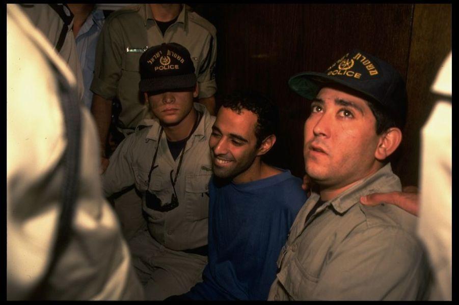 """« Le tueur à l'étrange sourire. Yigal Amir escorté, lundi 6 novembre, au palais de justice de Tel-Aviv : """"J'ai tué Rabin parce qu'il voulait donner notre pays aux Arabes"""".» - Paris Match n°2425, 16 novembre 1995"""