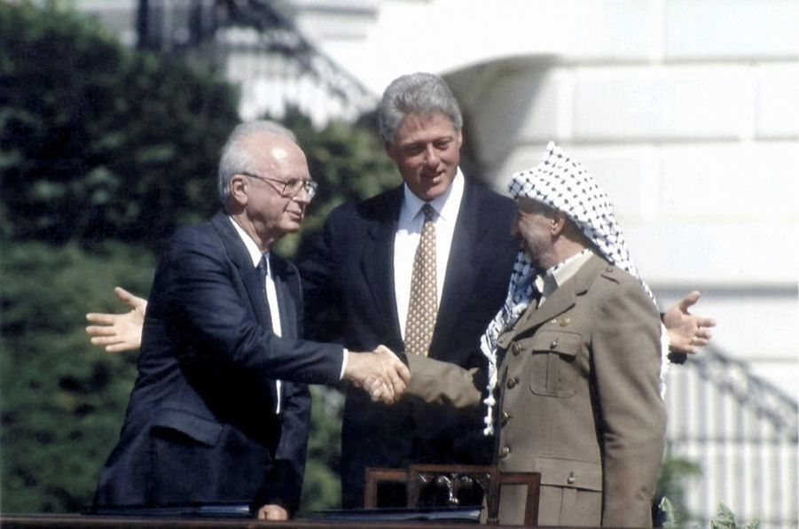 Pendant que Bill Clinton ouvre les bras comme pour embrasser la scène historique, les anciens ennemis Yitzhak Rabin et Yasser Arafat échangent une première poignée de main devant la table où ont été signés les accords, le 13 septembre 1993.