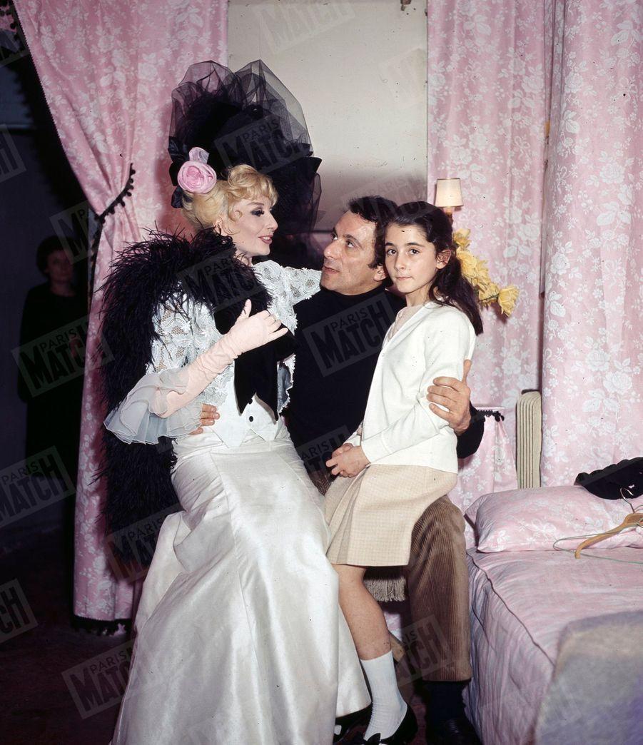 """Zizi Jeanmaire reçoit la visite de Roland Petit et de leur fille Valentine, dans sa loge du Palais Royal, où elle joue """"La dame de chez Maxim """"en décembre 1965."""