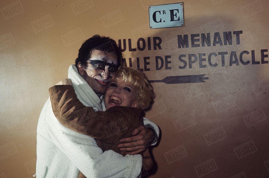 """Zizi Jeanmaire rend visite à Roland Petit, dans les coulisses de l'Opéra de Paris, où il interprète Quasimodo dans """"Notre Dame de Paris"""", en décembre 1965."""