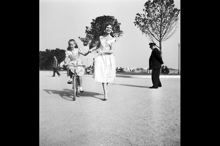 Au 8e Festival de Cannes : les deux jeunes comédiennes Brigitte Fossey et BB s'amusent sur la Croisette. Cannes, France. Mai 1955.