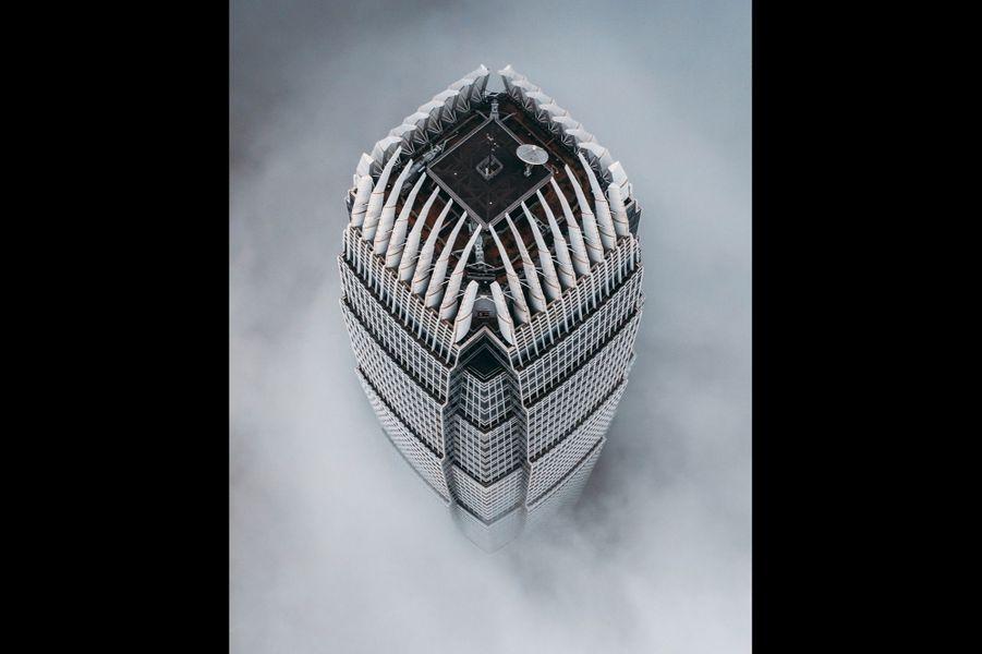 La tour iconique de Hong Kong, l'International Financial Centre, haute de 415 mètres, cernée par les nuages.