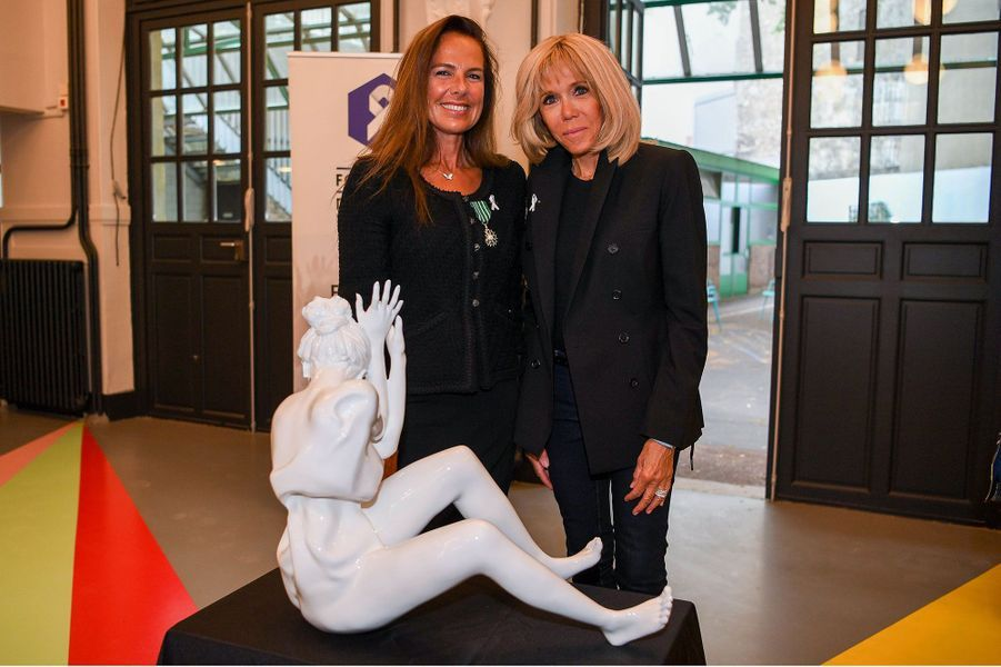 Laurence Jenkell et Brigitte Macron posent devant la sculpture de l'artiste.