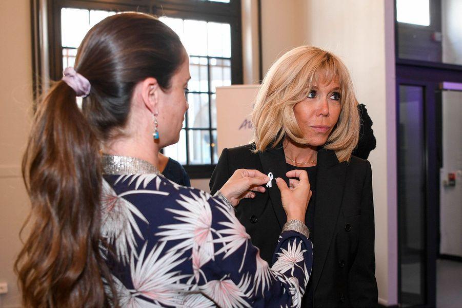 Anne-Cécile Mailfert remet à Brigitte Macron le ruban blanc, symbole de lalutte contre les violences faites auxfemmes.