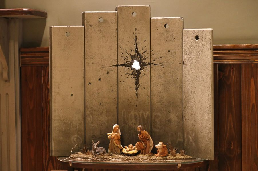 Des mini pans de mur, sur lesquels des tags appellent à la paix et à l'amour, servent d'arrière plan à une crèche posée sur une petite table, avec à son pied des cadeaux. L'impact de l'obus sur le mur fait penser à une étoile au dessus de Marie, Joseph et Jésus, entourés d'une vache et d'un âne.