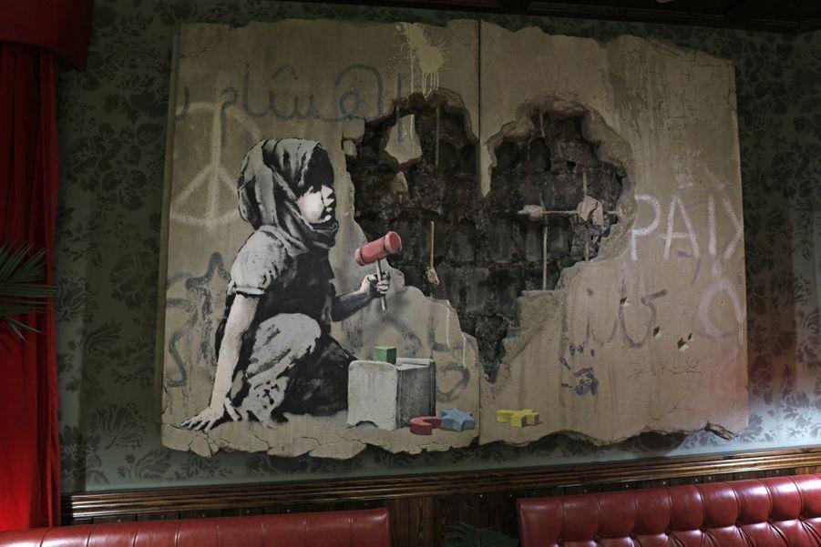 En 2005, Banksy avait peint neuf pochoirs --dont une échelle posée sur le mur ou une petite fille emportée par des ballons-- voulant mettre en évidence l'impact du mur sur la vie des Palestiniens.Le mur de sécurité est devenu à la fois un lieu de protestation et un terrain d'expression politico-artistique. Les fresques qui le recouvrent par endroits en font une attraction pour les touristes.