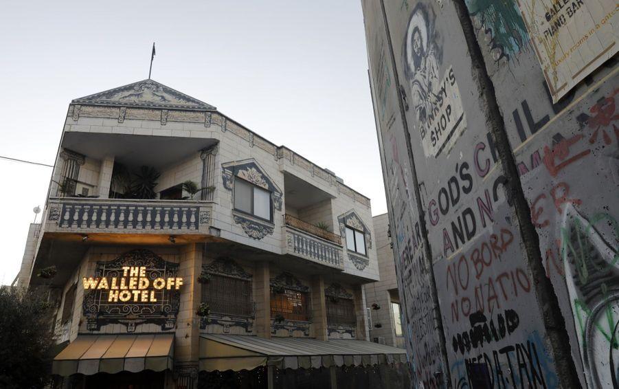 """Une petite crèche disposée devant des pans de mur transpercés par un obus: à quelques jours de Noël, la dernière oeuvre de l'artiste Banksy a été dévoilée dans la symbolique ville de Bethléem, en Cisjordanie occupée. Celle-ci est exposée dans l'entrée de l'hôtel """"Walled-Off"""" que Banksy a ouvert en 2017 dans la ville palestinienne et dont les chambres donnent sur le mur érigé par Israël et qui empiète en Cisjordanie."""