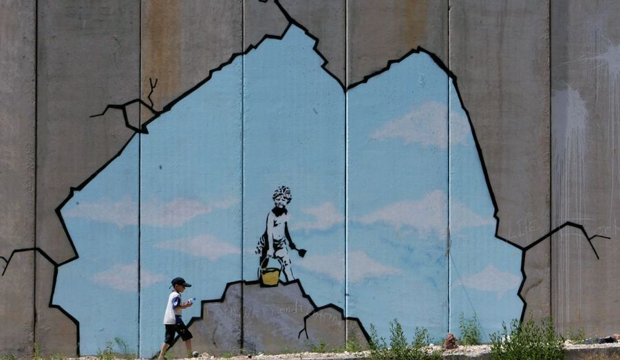 Des enfants qui font des châteaux de sable, des paysages fantastiques, une petite fille qui se laisse emporter par des ballons, en tout neuf oeuvres «décorent» le mur de Gaza. Avec son art, il dénonce l'injustice et pousse à la réflexion. Ses graffitis deviennent alors mondialement reconnues comme étant une voix dénonçant l'inégalité et la corruption.