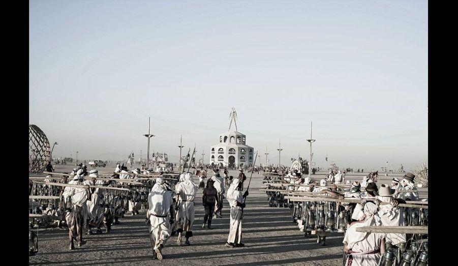 Des bénévoles vêtus de blanc chargés de bouteilles de pétrole vont alimenter les lampadaires. Au fond, la statue de bois monumentale de Burning Man.