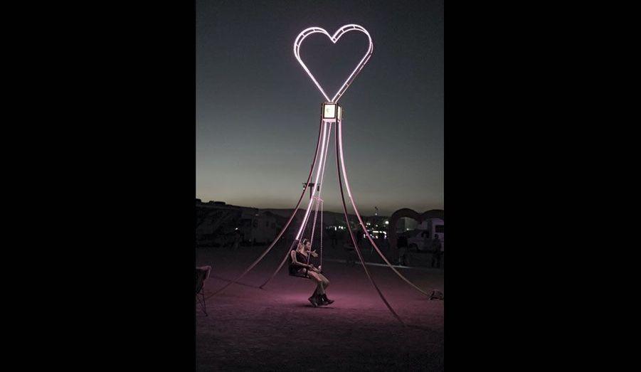 Sous un cœur de néon, deux amoureux sur une balançoire. Cet « Art Camp » est voué à la culture du rose. Les canapés et toutes les boissons offertes par les créateurs de l'« installation » sont « pink ».