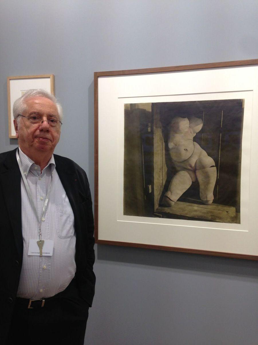 Le galerie Marcel Fleiss pose devant une photographie de poupée, 1920, de Hans Bellmer.