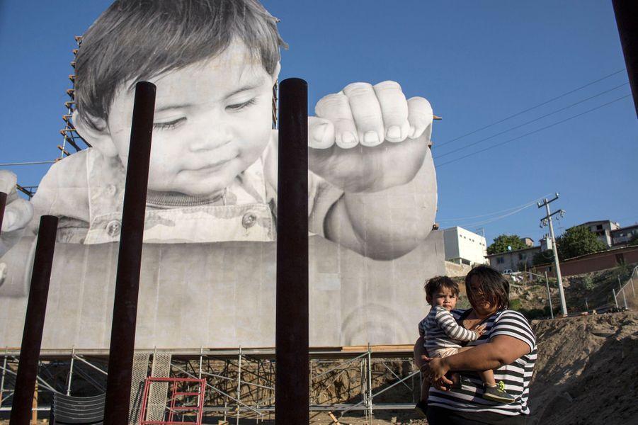 Dans les bras de sa mère, David Enrique, surnommé «Kikito», pose devant la photographie géante le représentant.